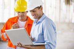 Manliga arkitekter som arbetar på bärbara datorn på konstruktionsplatsen Arkivfoto