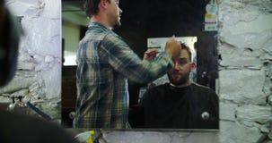 Manliga Barber Giving Client Haircut Reflected i spegel lager videofilmer