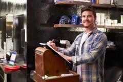 Manliga Barber Standing By Cash Register som skriver ner att boka royaltyfri bild