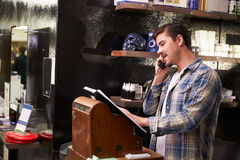 Manliga Barber Standing By Cash Register som tar bokning arkivbild