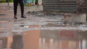 Manliga ben för närbild som går på den bostads- gården till och med den brutna smutsiga vägen med enorm pöl som mannen reflektera arkivfilmer