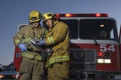 Manliga brandmän som läser dokumentet Royaltyfria Bilder