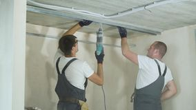 Manliga byggmästare som inomhus använder för metalldrywall för elektrisk drillborr monterande profiler på konstruktionsplats