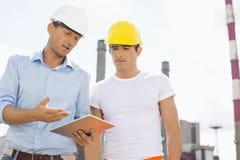 Manliga byggnadsarbetare som diskuterar över den digitala minnestavlan på bransch Royaltyfria Foton