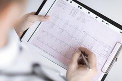 Manliga doktorshänder med kardiogrammet arkivfoto