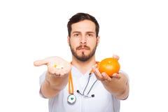 Manliga doktorsvisningapelsin och preventivpillerar royaltyfria bilder