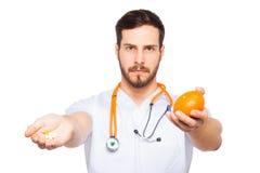 Manliga doktorsvisningapelsin och preventivpillerar royaltyfri foto
