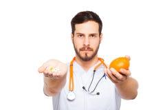 Manliga doktorsvisningapelsin och preventivpillerar royaltyfri fotografi