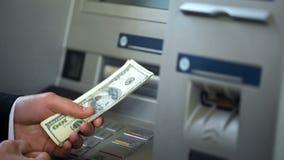 Manliga fående dollar från maskinen för automatisk kassör, kassa som återtar och att packa ihop royaltyfria bilder