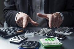 Manliga finansiella couting marginaler och kostnader på hans skrivbord arkivfoto