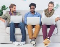 Manliga formgivare som arbetar samman med bärbara datorer Arkivbild