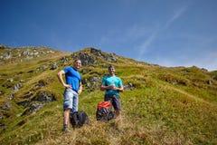 Manliga fotvandrare på en bergslinga Arkivfoton