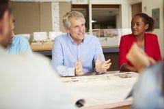 Manliga framstickandeLeading Meeting Of arkitekter som sitter på tabellen royaltyfri foto