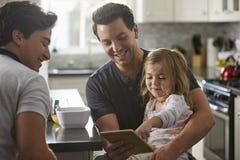 Manliga glade farsor använder minnestavlan med dottern i kök, slut upp arkivbilder