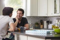 Manliga glade par i deras 20-tal som talar i deras kök Arkivfoton