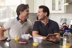 Manliga glade par i kök med minnestavlan som ser de Royaltyfria Foton