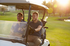 Manliga golfare som kör barnvagnen längs farled av golfbanan arkivfoton