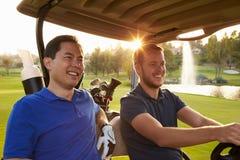 Manliga golfare som kör barnvagnen längs farled av golfbanan arkivbild