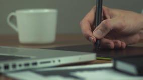 Manliga händer av att använda teckningsminnestavlan Märkes- arbete med diagramminnestavlan arkivfilmer