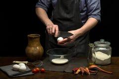 Manliga händer bryter ett ägg in i den glass bunken för att göra deg arkivfoton
