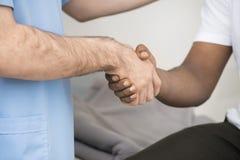 Manliga händer för doktor And Patient Shaking efter CT-bildläsning Arkivbild