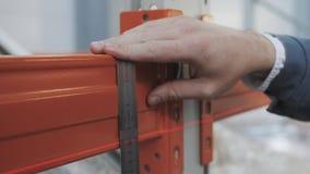 Manliga händer för ` s med precision som mäter hjälpmedlet Teknikern Makes Measurement av strålen på lagringen, slut sköt upp lager videofilmer