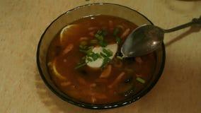 Manliga händer häller sammelsuriumsoppa i en bunke Solyanka soup för ryss för borschtcloseupkokkonst arkivfilmer