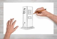 Manliga händer i den nära sikten som drar en gaspump med en svart blyertspenna på papper som förläggas på en trätabell Arkivfoton