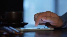 Manliga händer i tumvanten genom att använda den smarta telefonen arkivfilmer