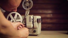 Manliga händer inkluderar en gammal filmprojektor arkivfilmer