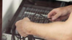 Manliga händer rymmer svarta kablar på oskarp bakgrund av elektroniskt material arkivfilmer