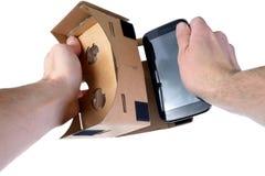 Manliga händer sätter in mobiltelefonen in i VR-exponeringsglaspapp royaltyfria bilder