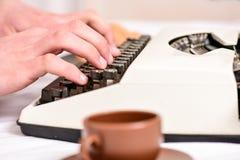 Manliga händer skriver berättelse eller rapporten genom att använda upp det vita slutet för tappningskrivmaskinsutrustning Skriva royaltyfri foto
