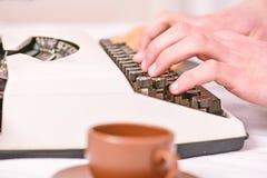 Manliga händer skriver berättelse eller rapporten genom att använda upp det vita slutet för tappningskrivmaskinsutrustning Skriva arkivfoton