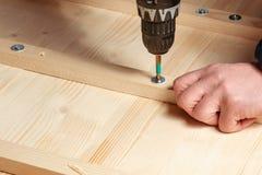 Manliga händer skruvar träkvarter till brädena med en skruvmejsel arkivfoton