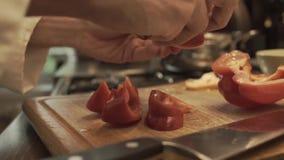 Manliga händer som förbereder paprika på ett trämatlagningbräde