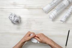 Manliga händer som river en dålig arkitekt som drar till styckena Nervöst villkor Arkivfoton