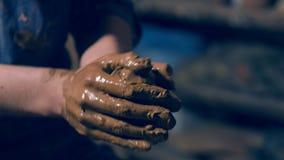Manliga händer som rymmer bollen gjord av lera stock video
