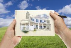 Manliga händer som rymmer som är pappers- med huset som drar över tomt gräsfält Royaltyfri Bild