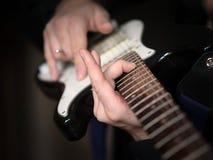 Manliga händer som spelar på den elektriska gitarren, slut upp, utvald fokus royaltyfri bild