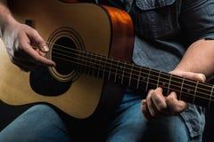 Manliga händer spelar den akustiska gitarren Royaltyfri Bild