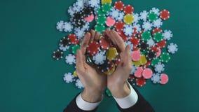 Manliga hållande handfullpokerchiper, liten förmögenhet för segrar i kasinot, dobbleri stock video