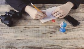 Manliga händer över kafébakgrund - bordlägga träplankor, smartphonen, nootbook, blyertspennan, jordklotet, kikare, flaggan, syfte Arkivbilder