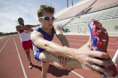 Manliga idrottsman nen som sträcker på löparbana Arkivbild