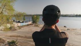 Manliga kamera för cyklistinnehavtelefon och tabilder av floden, bron och staden Den uppsökte cyklisten som gör foto med hans tel lager videofilmer