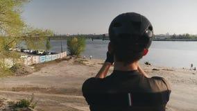 Manliga kamera f?r cyklistinnehavtelefon och tabilder av floden, bron och staden Den upps?kte cyklisten som g?r foto med hans tel arkivfilmer