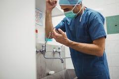 Manliga kirurgtvagninghänder före operation genom att använda den korrekta tekniken för renlighet Arkivfoto