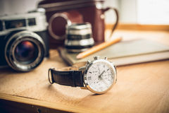Manliga klockor som ligger på tabellen mot retro uppsättning för fotografi Arkivbild
