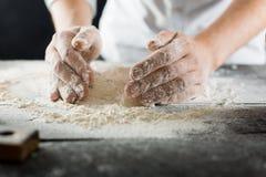 Manliga kockhänder knådar degen med mjöl på köksbordet arkivfoto