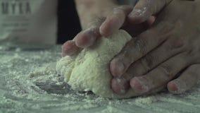 Manliga kockhänder knådar deg med mjöl på köksbordet arkivfilmer